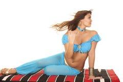 Женщина на одеяле в голубом дуновении волос смотрит назад стоковая фотография rf