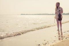 Женщина на пляже около моря держа скрипку Стоковое Изображение