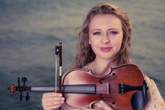 Женщина на пляже около моря держа скрипку стоковое фото