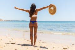 Женщина на пляже стоя с оружиями протягивала против моря бирюзы Вид сзади женского нося бикини с поднятыми руками Carefr стоковое фото rf