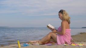 Женщина на пляже читая книгу