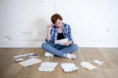 Женщина на поле живущей комнаты с калькулятором и банком и счеты обработка документов и документы делая отечественный финансовый  Стоковые Фотографии RF