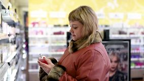 Женщина на предпосылке полок с косметиками и духами выбирает духи видеоматериал