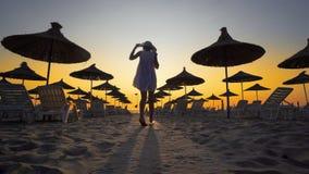 Женщина на пустом пляже на заходе солнца Стоковые Фото