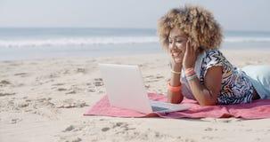 Женщина на пляже используя компьютер Стоковые Фотографии RF