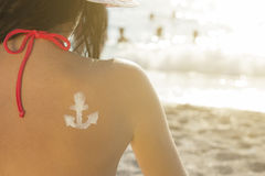 Женщина на пляже с чертежом анкера сливк солнца на ей назад Стоковые Изображения