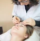 Женщина на салоне для профессиональный формировать брови стоковая фотография