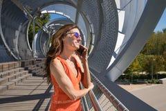Женщина на современном населенном пункте городского типа говоря на черни Стоковые Изображения