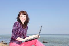 Женщина на солнечном пляже работая на компьтер-книжке Стоковое фото RF