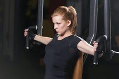 Женщина на спортзале спорта делая тренировки оружий на машине Стоковое Изображение
