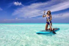 Женщина на стойки доске МАЛЕНЬКОГО ГЛОТКА затвора вверх над тропическим морем стоковые фотографии rf