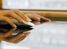 Женщина на таблице офиса держит мышь компьютера Стоковые Фотографии RF