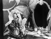 Женщина на таблице шлихты прикладывая косметики Стоковые Изображения RF