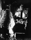 Женщина на таблице шлихты смотря в зеркале (все показанные люди более длинные живущие и никакое имущество не существует Гарантии  Стоковые Фотографии RF