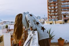 Женщина на террасе на крыше, смотря вниз, с волосами понижаясь I Стоковое Фото