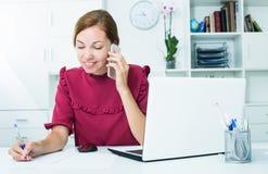 Женщина на телефоне на работе Стоковые Изображения