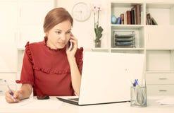 Женщина на телефоне с компьтер-книжкой Стоковые Изображения RF