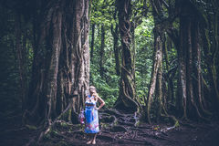 Женщина на тропической балийской предпосылке ландшафта, к северу от острова Бали, Индонезия Стоящее близко дерево фикуса Стоковое Фото
