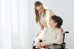Женщина на усмехаться кресло-коляскы и попечителя Стоковая Фотография RF