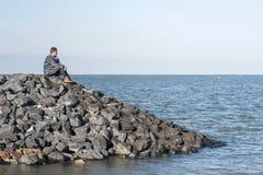 Женщина на утесах рассматривая море стоковые изображения