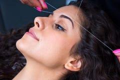 Женщина на удалении волос на лице продевая нитку процедуру стоковое изображение