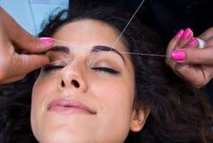 Женщина на удалении волос на лице продевая нитку процедуру стоковые изображения