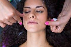 Женщина на удалении волос на лице продевая нитку процедуру Стоковые Изображения RF