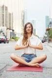 Женщина на улице города городской делая йогу Стоковое Фото