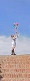 Женщина на шагах улавливает красочные цветки Стоковое Изображение
