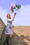 Женщина на шагах улавливает красочные цветки i Стоковое фото RF