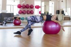 Женщина на шарике в спортзале стоковые фотографии rf