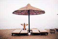 Женщина на южном пляже отдыхая в шезлонге под зонтиком детеныши женщины острова formentera пляжа Флюиды пляжа Стоковое Фото