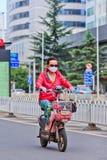 Женщина на e-велосипеде в центре города, Kunming, Китае Стоковая Фотография RF
