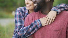 Женщина нежно обнимая, счастливые люди чернокожего человека и смешанной гонки усмехаясь совместно акции видеоматериалы