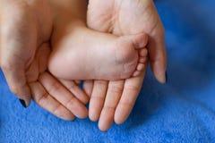 Женщина нежно обняла ноги ` s младенца Стоковая Фотография RF