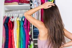 Женщина нерешительности выбирая обмундирование в шкафе одежд стоковые фотографии rf