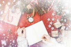 Женщина Нового Года состава рождества пишет что-то в пустом n стоковые изображения rf