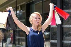 женщина ног принципиальной схемы мешка предпосылки ходя по магазинам белая Дама с белокурыми волосами и усмехаясь стороной Стоковое фото RF