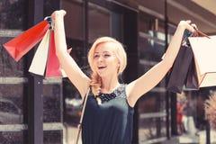 женщина ног принципиальной схемы мешка предпосылки ходя по магазинам белая Дама с белокурыми волосами и усмехаясь стороной стоковые фото