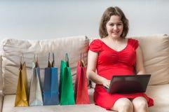 женщина ног принципиальной схемы мешка предпосылки ходя по магазинам белая Молодая милая женщина сидит на софе и ходить по магази Стоковые Фотографии RF