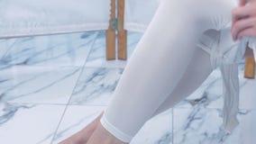 Женщина носит белый костюм нейлона для массажа ipg Ноги закрывают вверх сток-видео