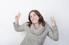 Женщина носит одежды зимы и делает жест победы Стоковая Фотография RF