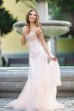 Женщина носит bridal платье около фонтана стоковое фото