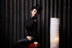Женщина нося верхнюю шляпу сидит на стуле в темной комнате стоковая фотография rf