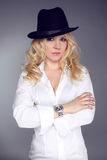 Женщина нося в белой рубашке и черной шляпе изолированных на задней части серого цвета Стоковое Изображение RF