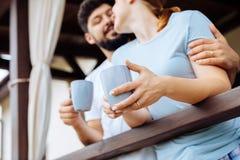 Женщина нося голубой чай утра обручального кольца рубашки и выпивая стоковое изображение