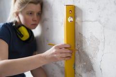 Женщина нося голубую рубашку используя выравнивать инструмент дома стоковое изображение