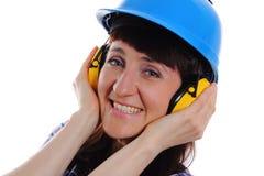 Женщина нося защитные шлем и наушники Стоковая Фотография