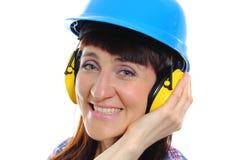 Женщина нося защитные шлем и наушники Стоковые Изображения RF