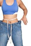 Женщина нося и показывая джинсыы слишком большой джинсовой ткани стоковые фотографии rf